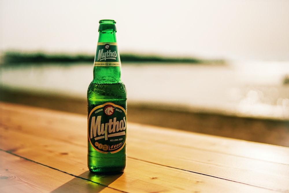 Mythos beer bottle on wooden table near beach