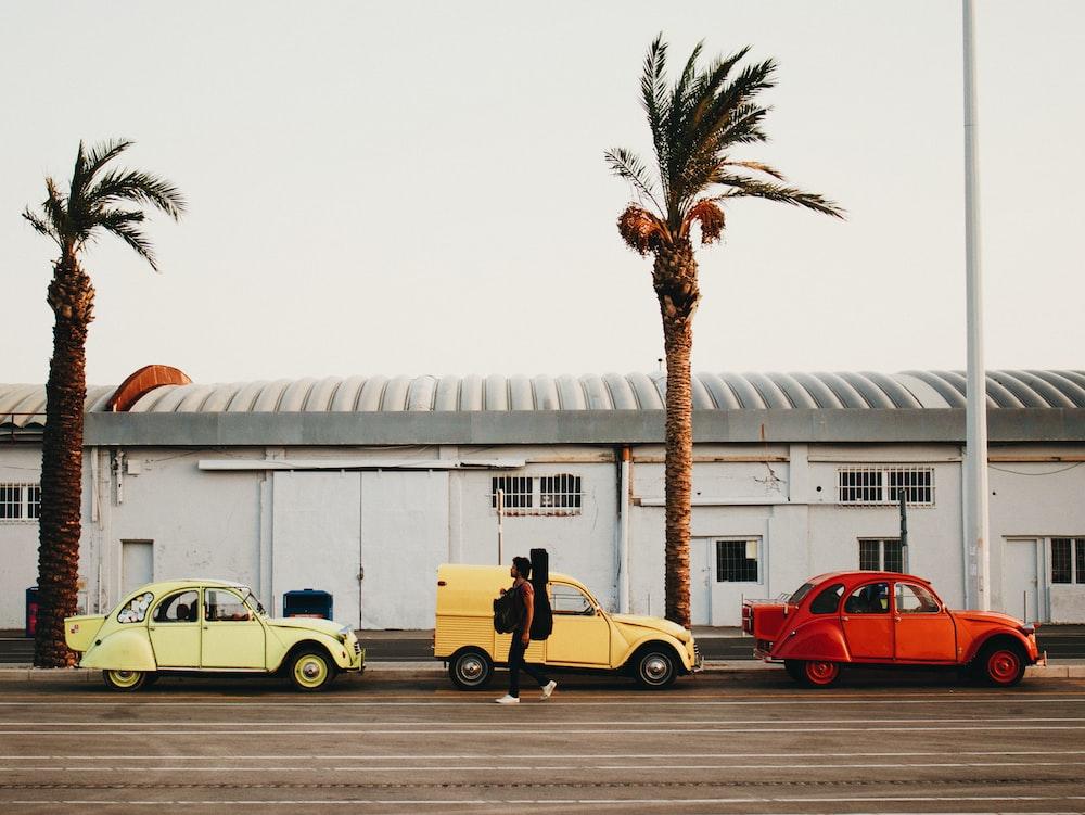 man walking beside three vehicles