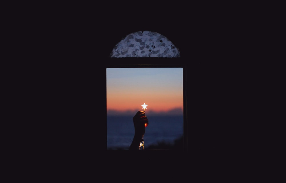 persona holding star near the window during sunset