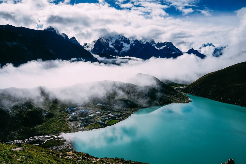 calm lake on green tree-covered mountains under cloudy skies