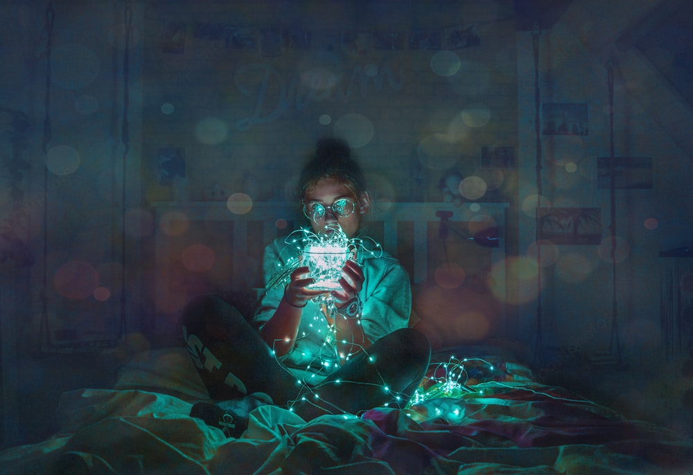 person holding green string LED light sitting on bed sheet