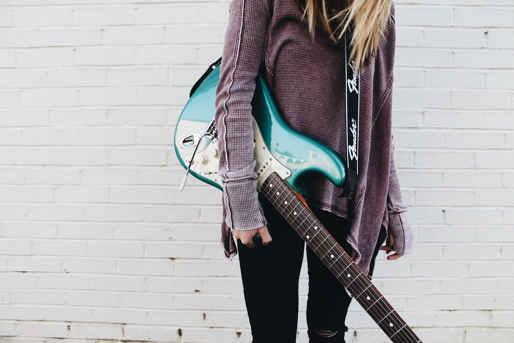 woman carrying green stratocaster guitar