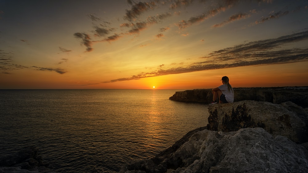 woman sitting on top of the cliff looking at the horizon of sunrise near body of water