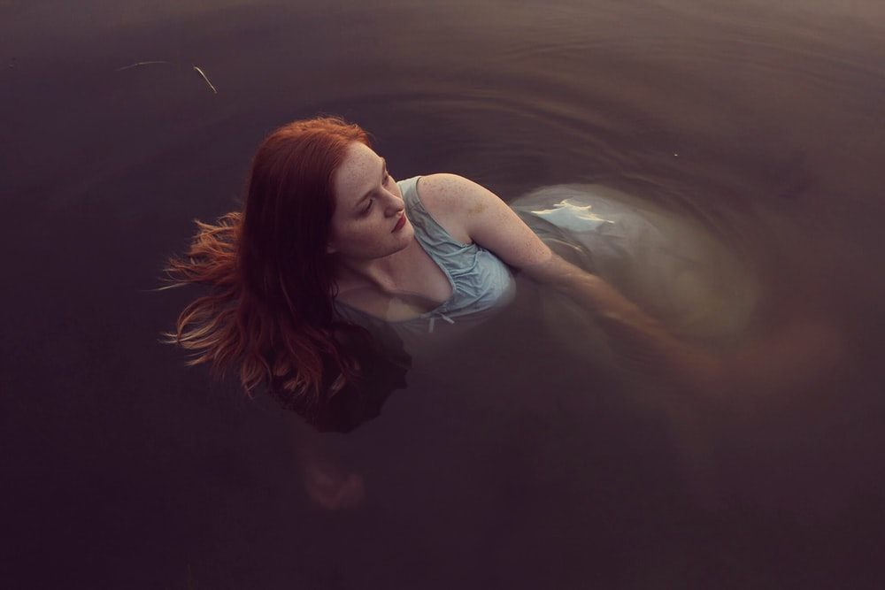 woman in gray tank dress lying on body of water during daytime