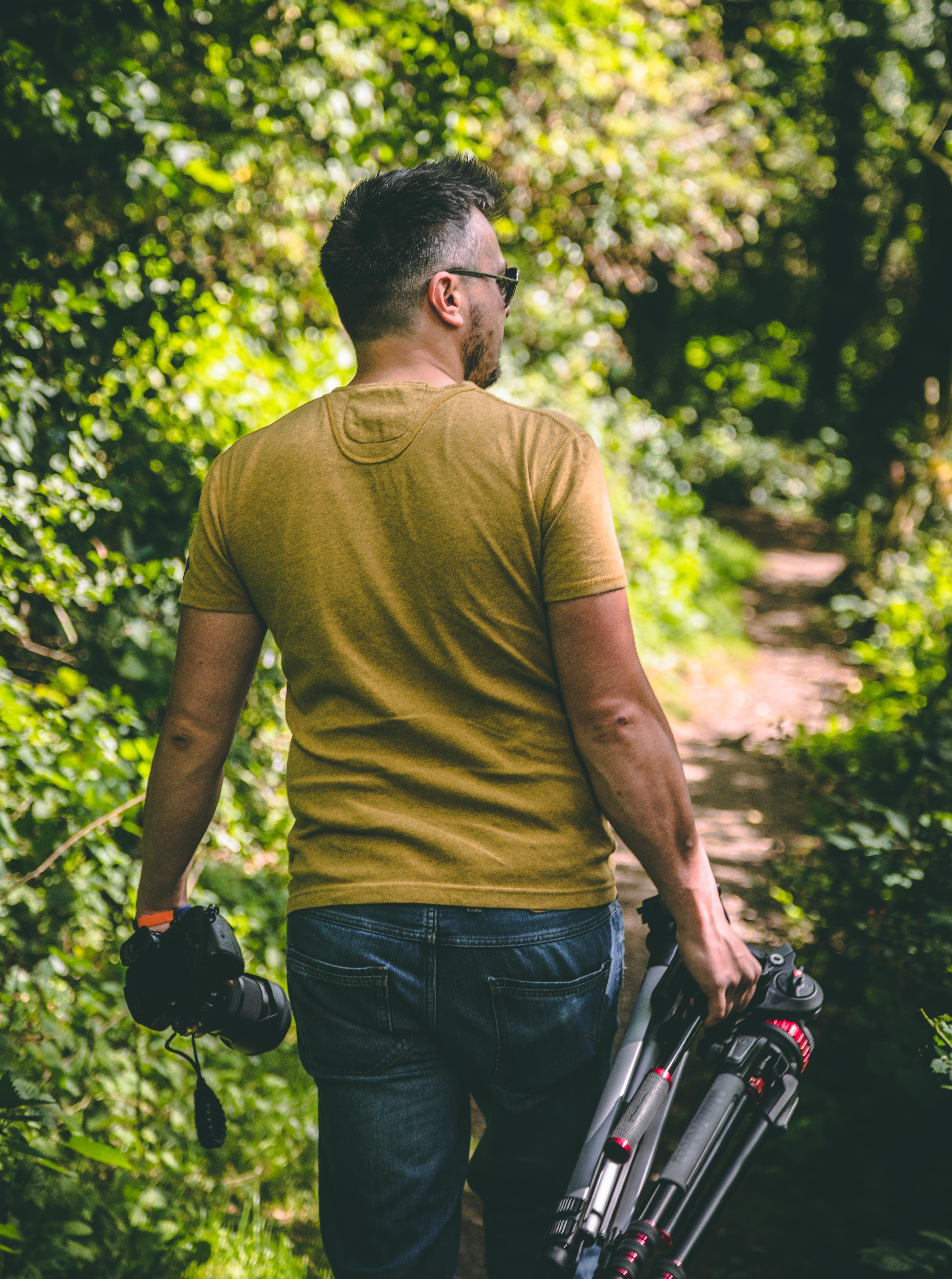 man wearing yellow T-shirt holding tripod and DSLR camera