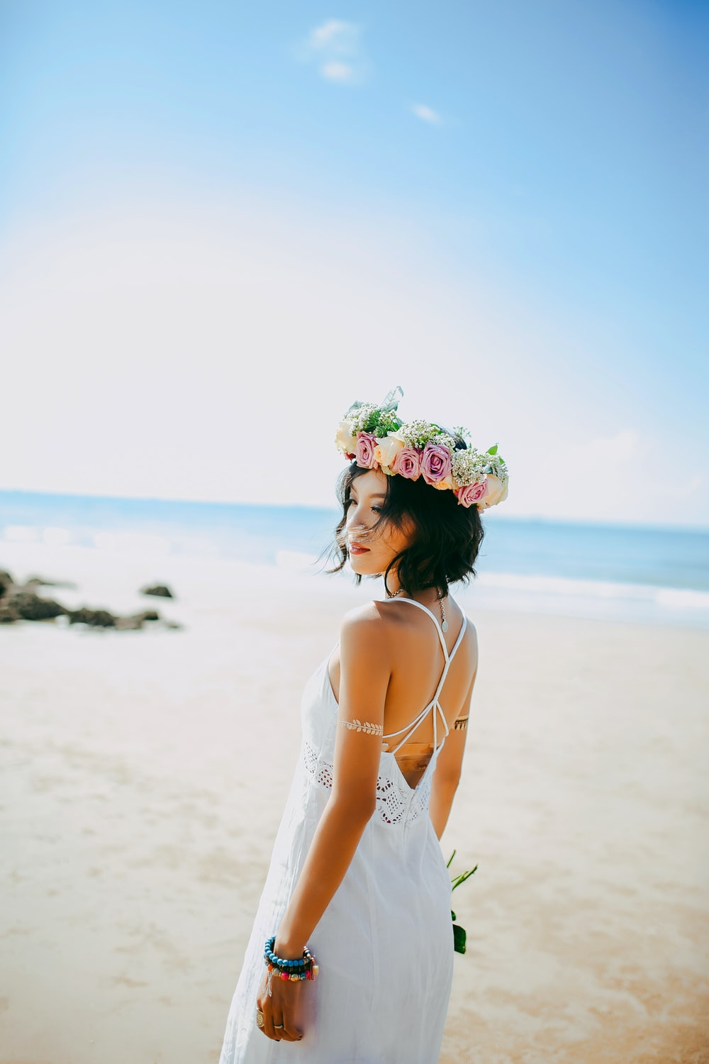 woman wearing white spaghetti-strap dress standing on the seashore during daytime photography