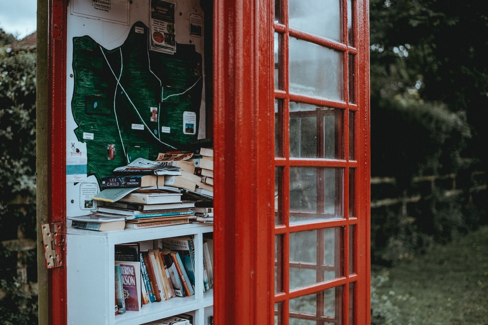 red telephone booth with book shelves beside of brick wall during daytime