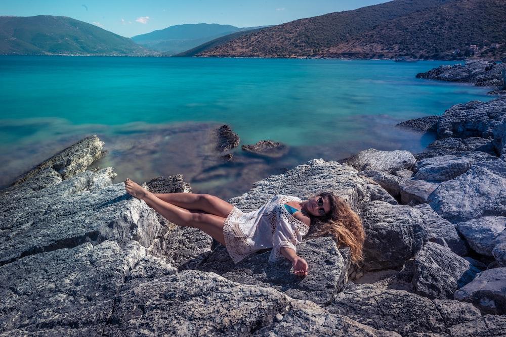 woman lying on gray rock near lake