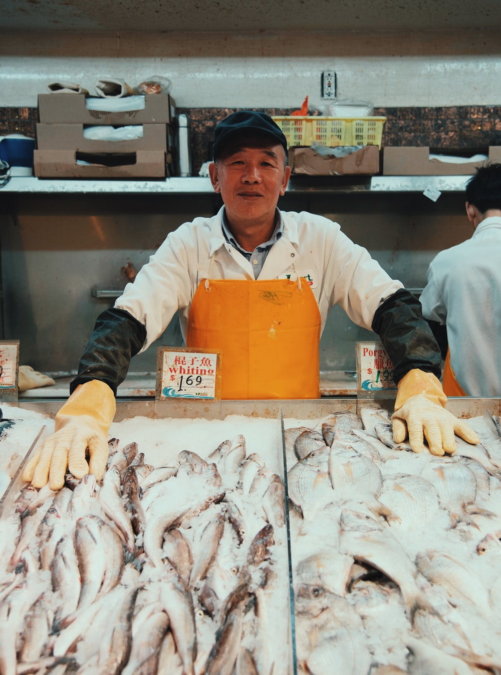 man wearing white polo shirt and brown apron standing near fish stands