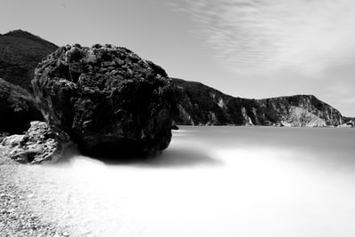 grayscale photo of coastline surrounded with rocky cliffs