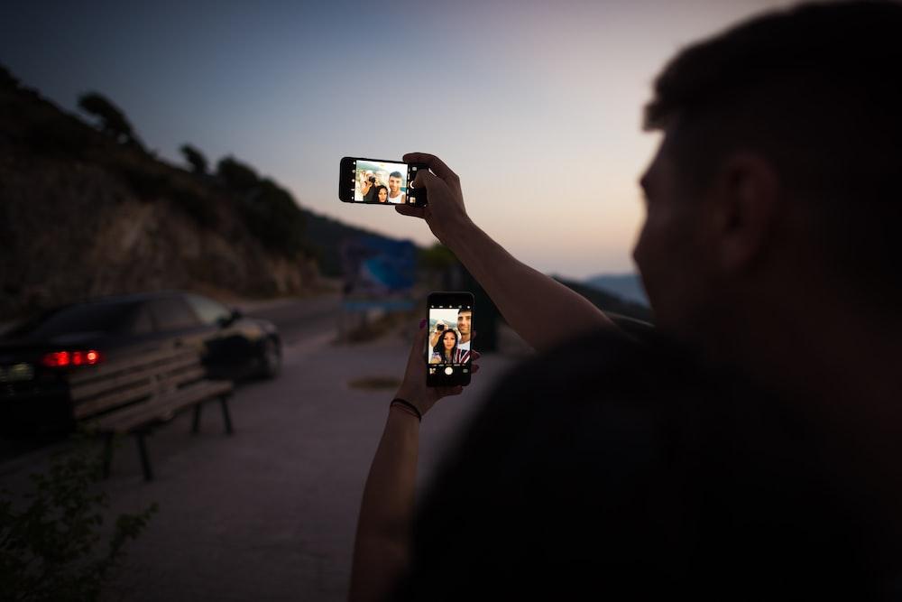 man holding smartphone during daytime