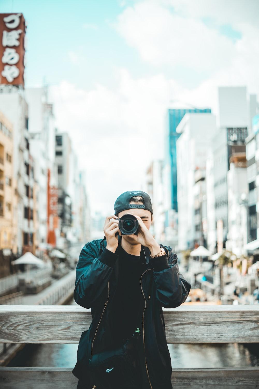 man wearing black jacket and cap holding DSLR camera during daytime