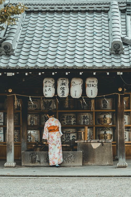 Woman wearing orange & white kimono dress standing near the house