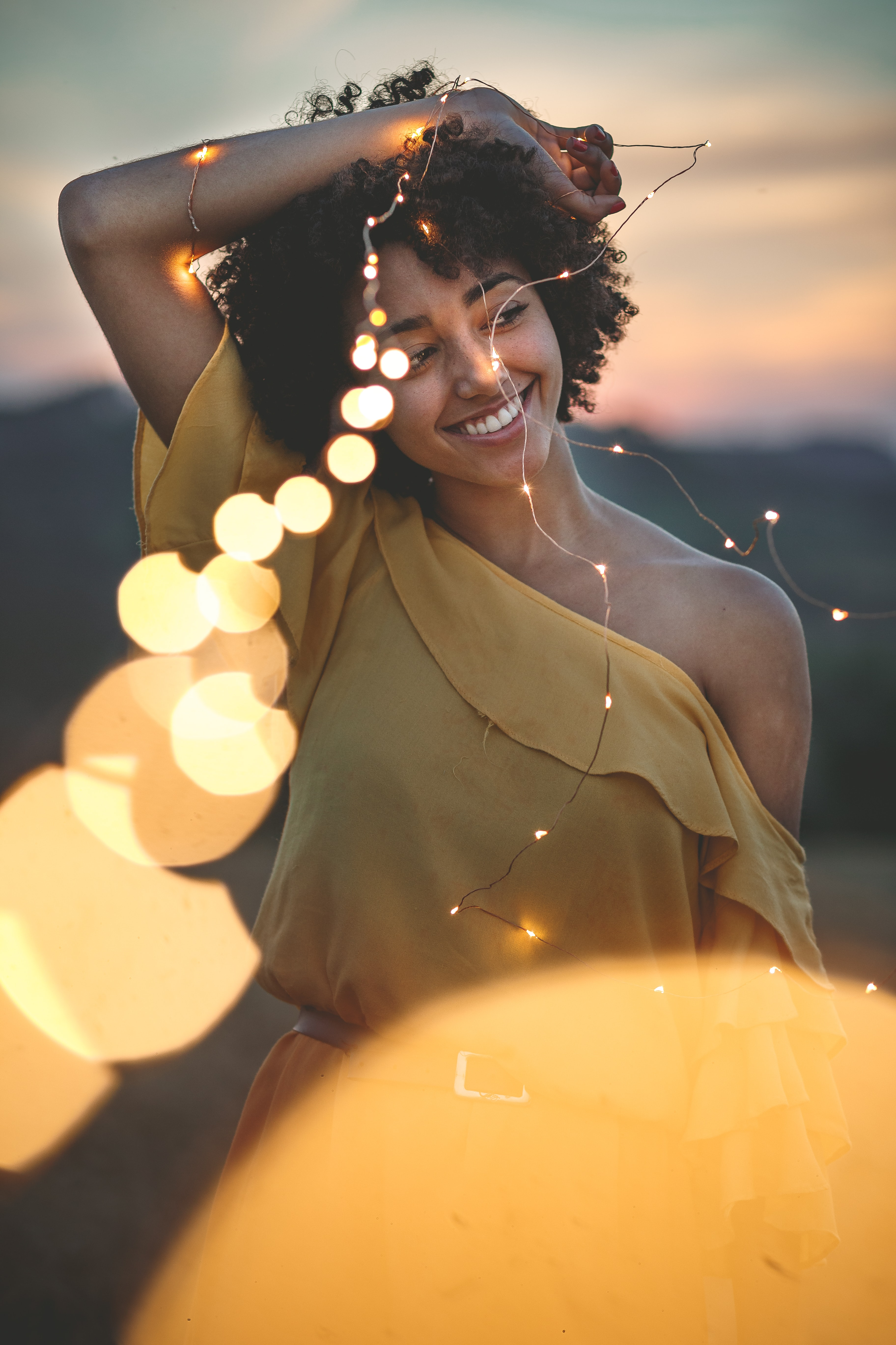 woman smiling while holding string lights