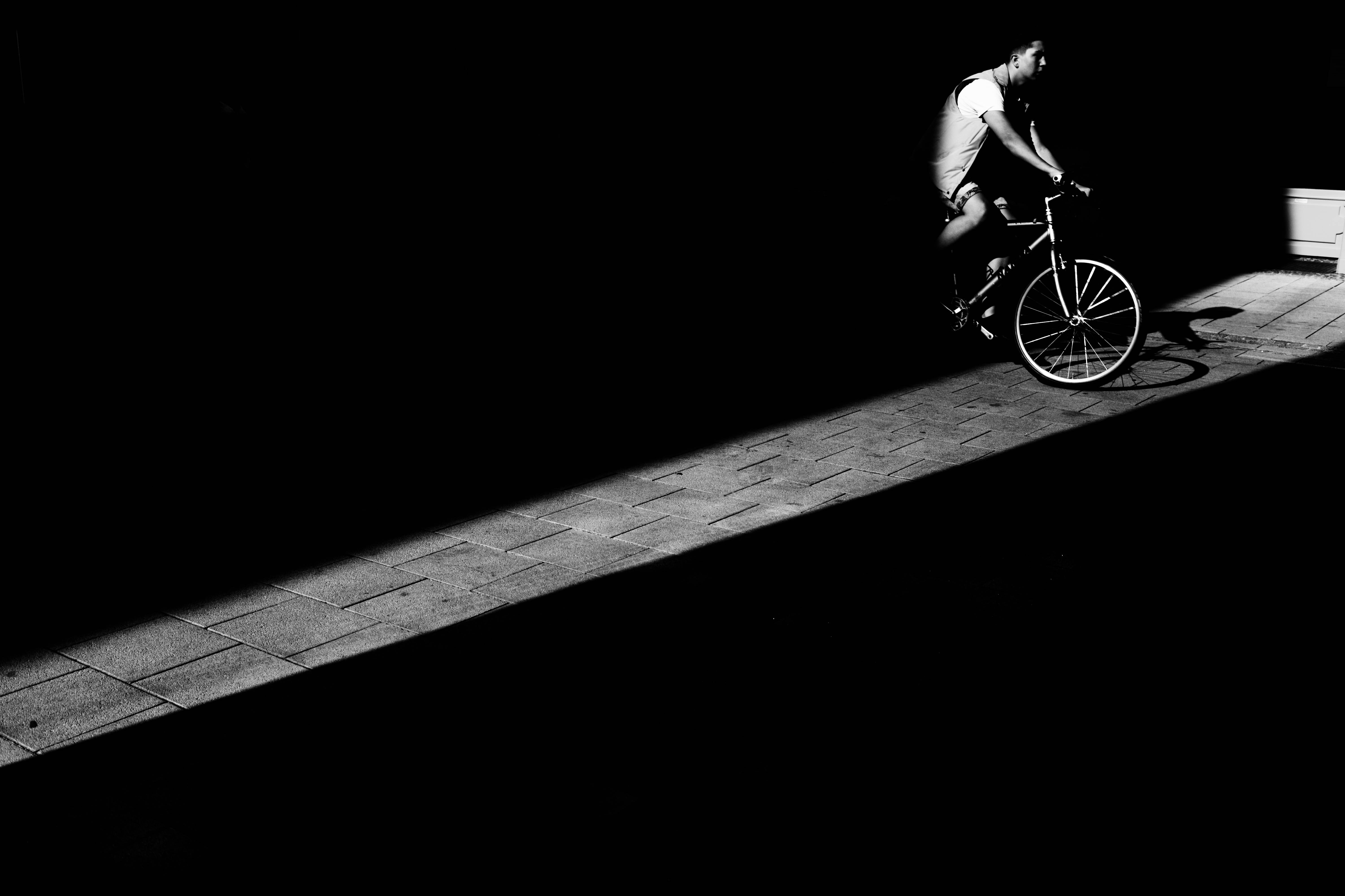 man riding bicycle in dark area