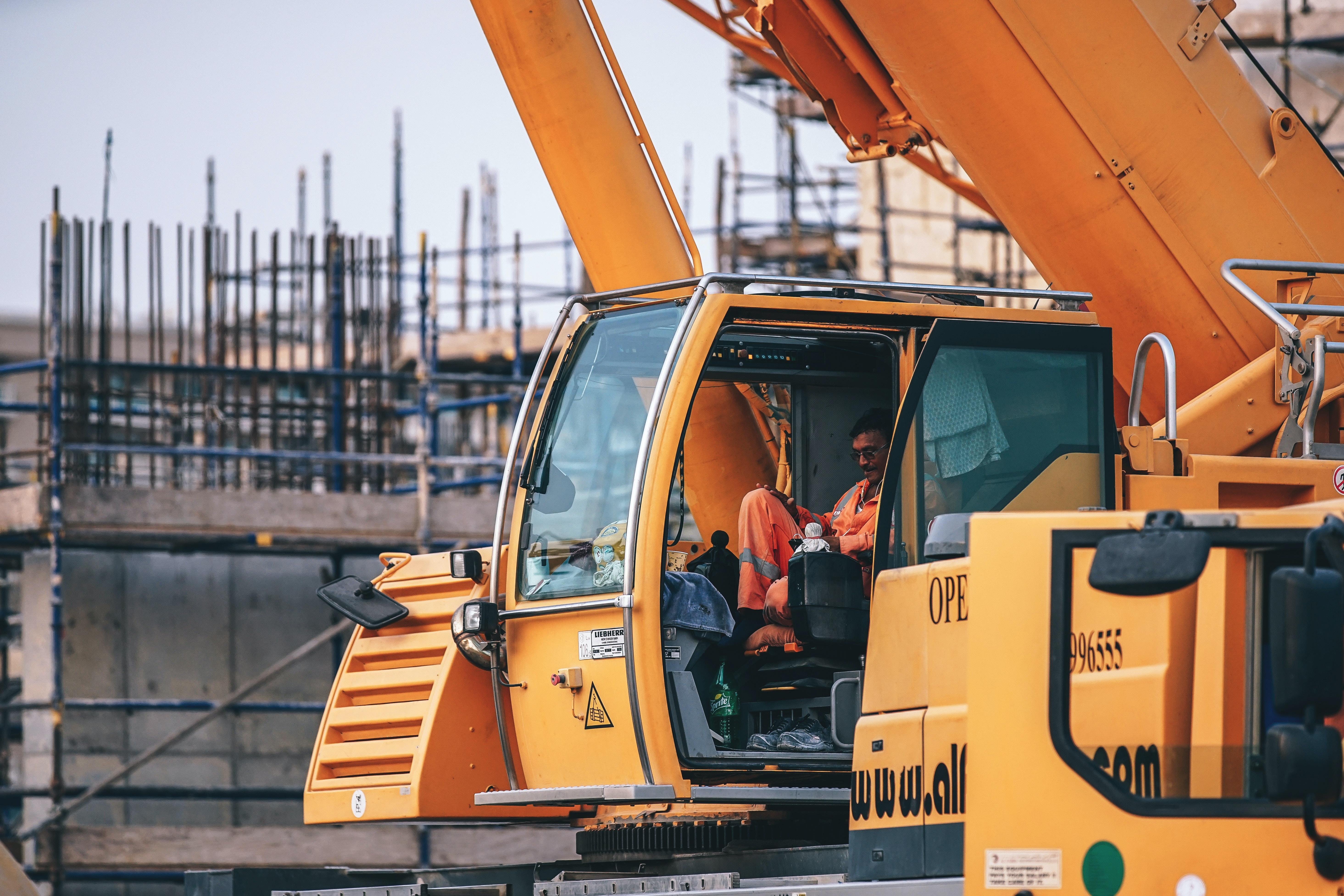 man riding orange heavy equipment at daytime
