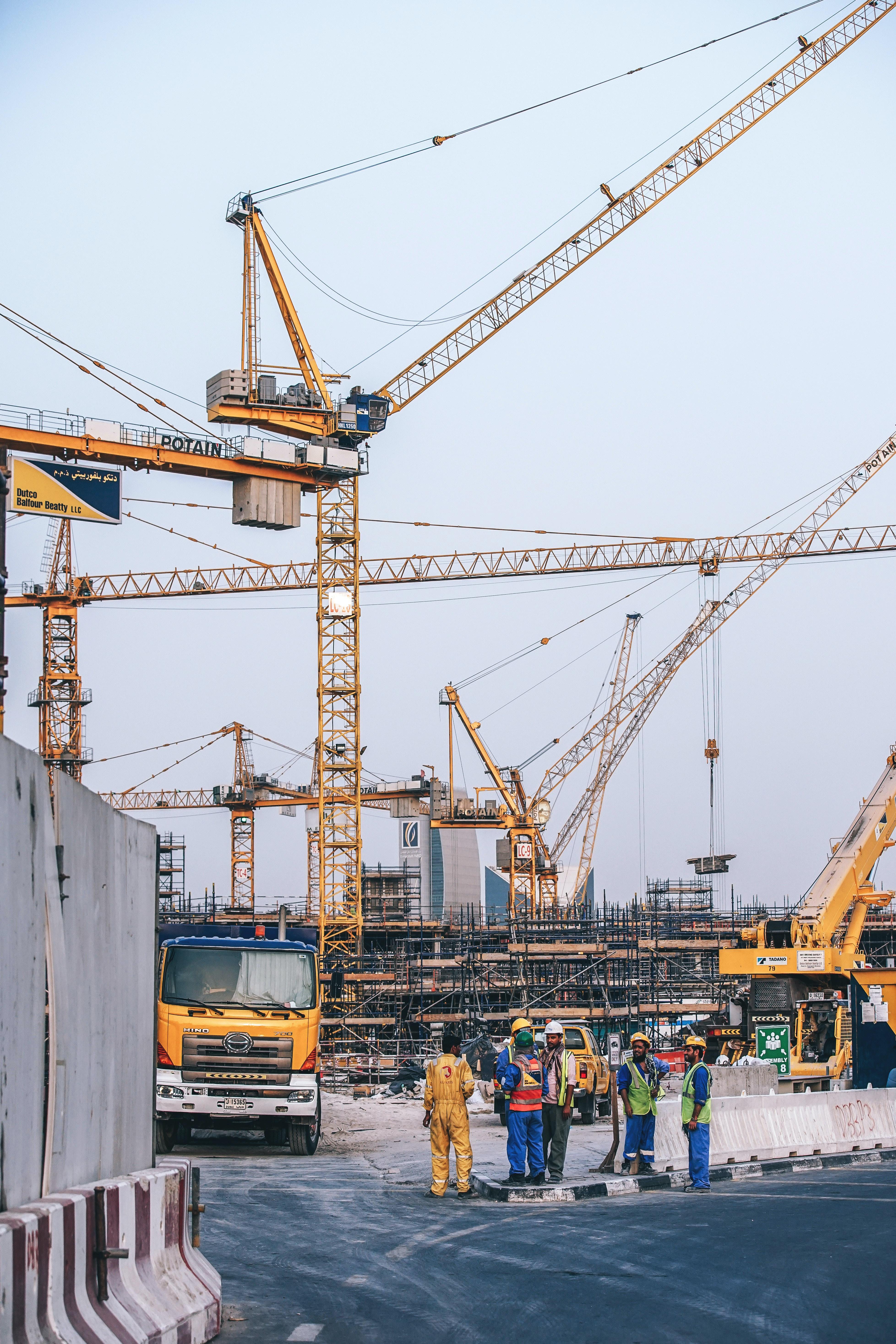 people standing under yellow metal cranes