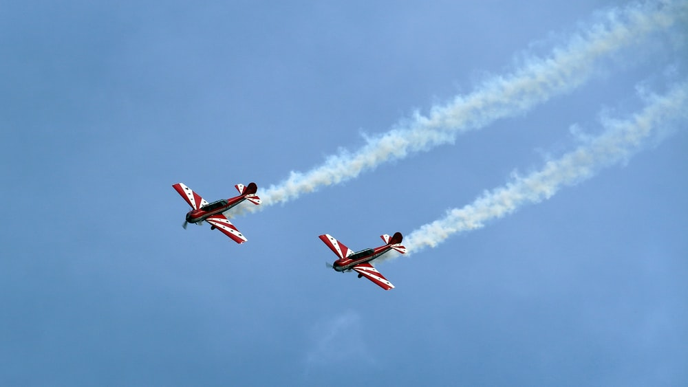 tow red-and-white planes under clear blue sky