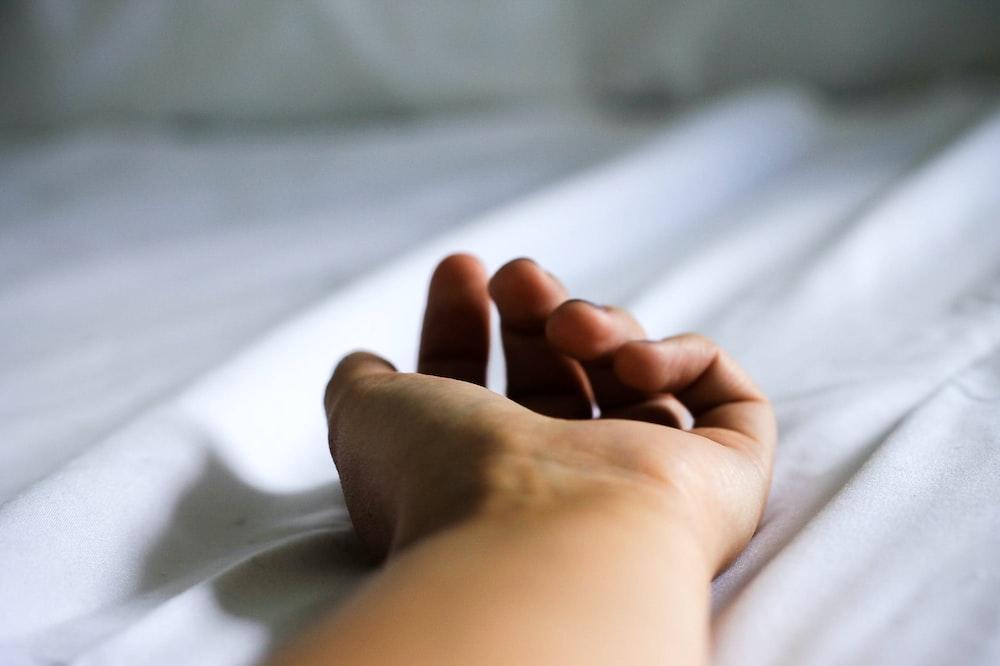 human hand on white textile