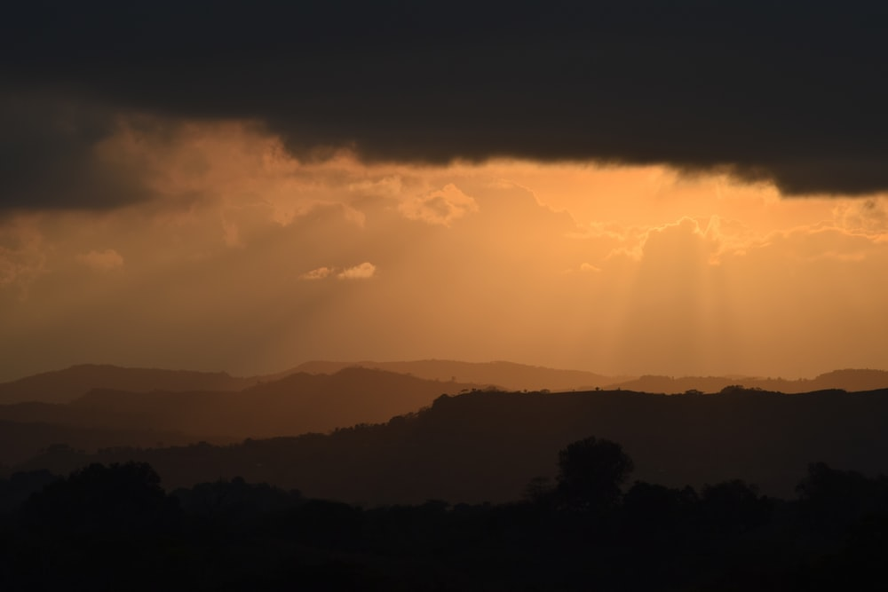 silhouette of mountain under black clouds