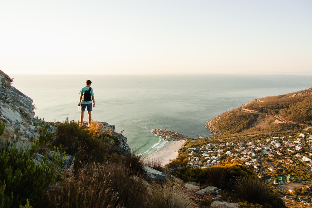 person standing on the edge of cliff overlooking body of water