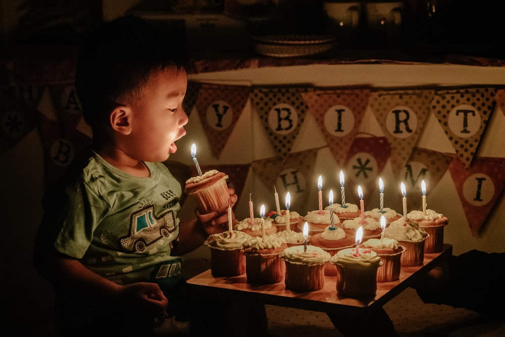 boy holding cupcake blowing the candle