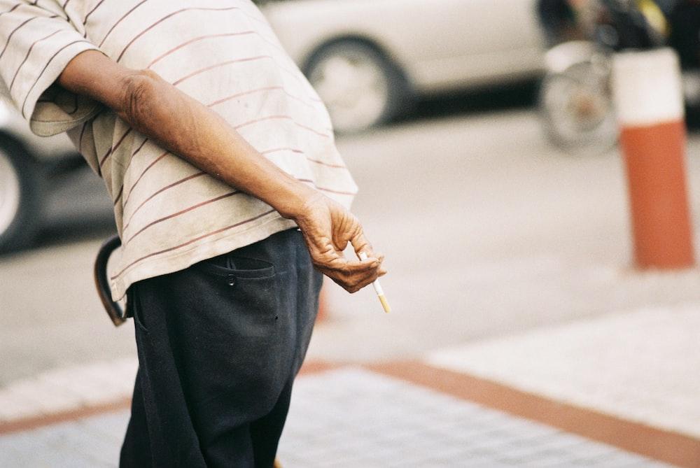 tilt-shift lens photography of man holding stick of cigarette during daytime