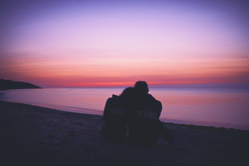 man and woman hugging each other on seashore during sunset