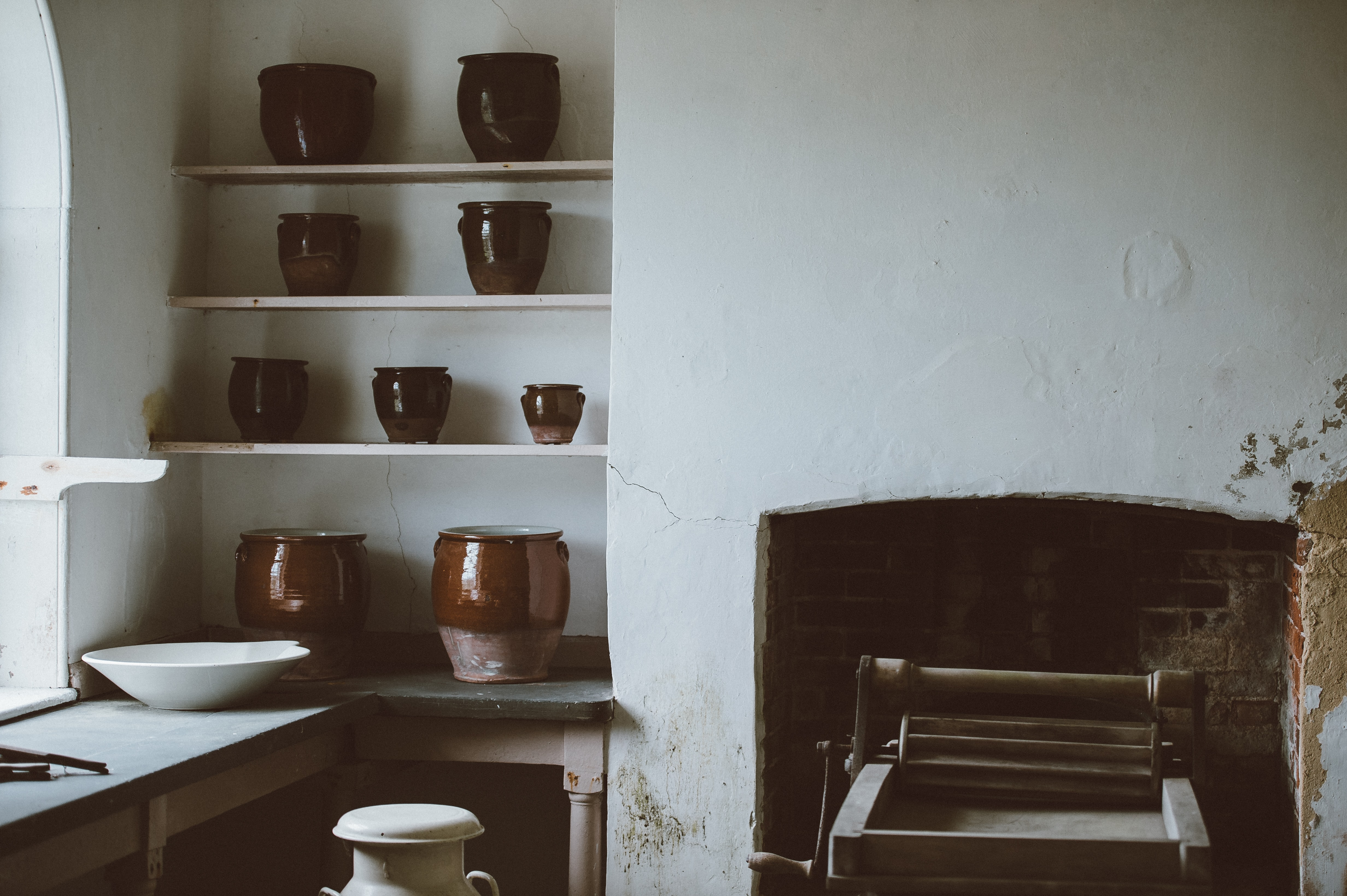photo of brown clay pots on rack in kitchen