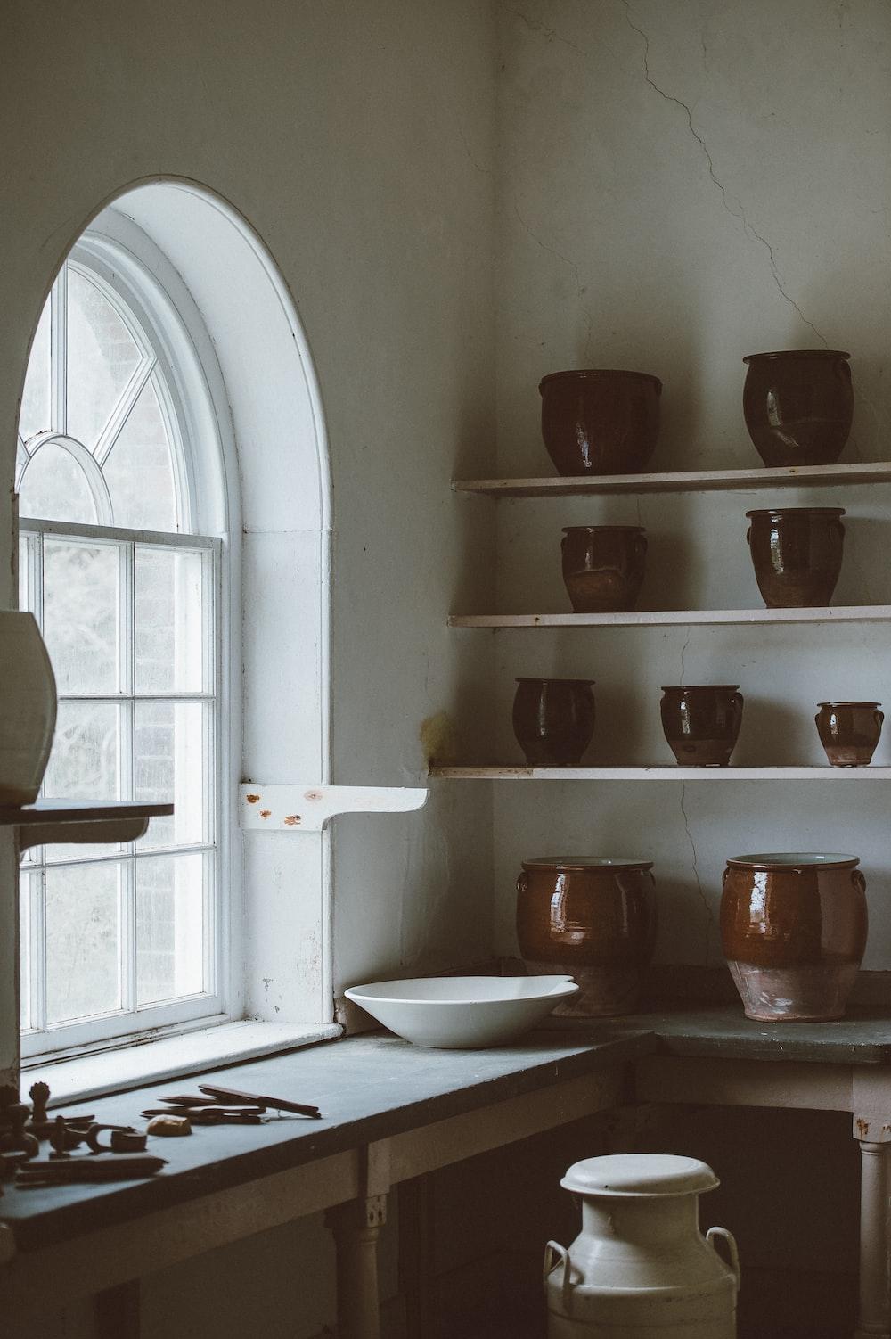 white ceramic bowl beside glass window