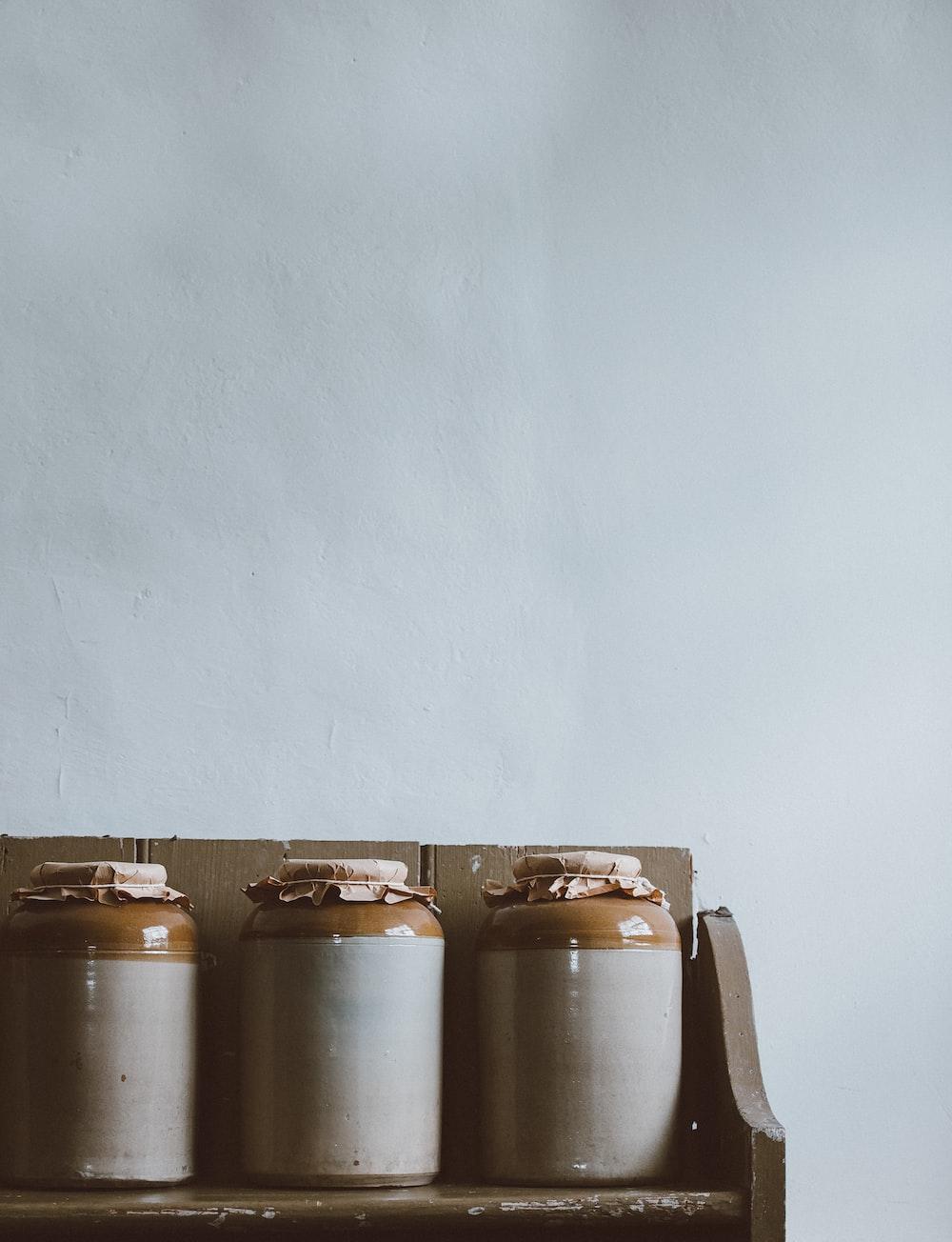 three white-and-brown ceramic jars on brown wooden rack