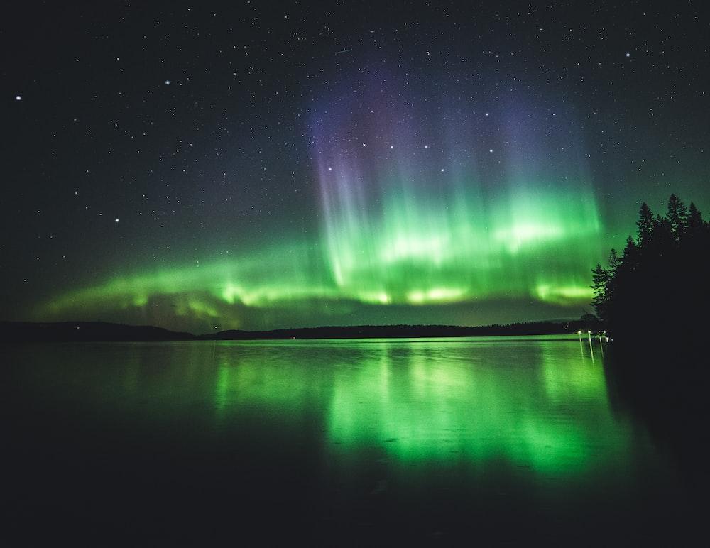 calm body of water under aurora lights