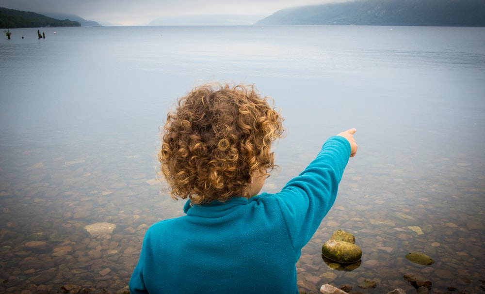 boy in blue turtleneck sweater pointing his finger on water