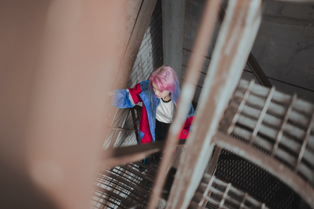 selective-focus photography of woman climbing metal stairs during daytime