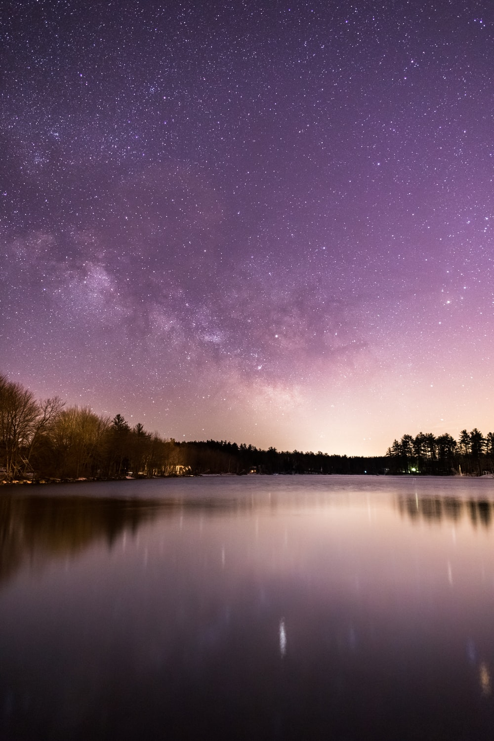 calm body of water overlooking trees under milky way