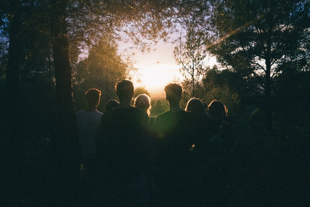 several people watching the sunrise in the middle of forest