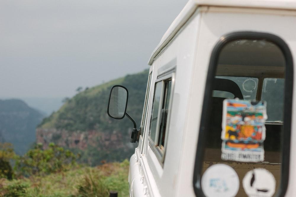 white vehicle facing green grass mountains