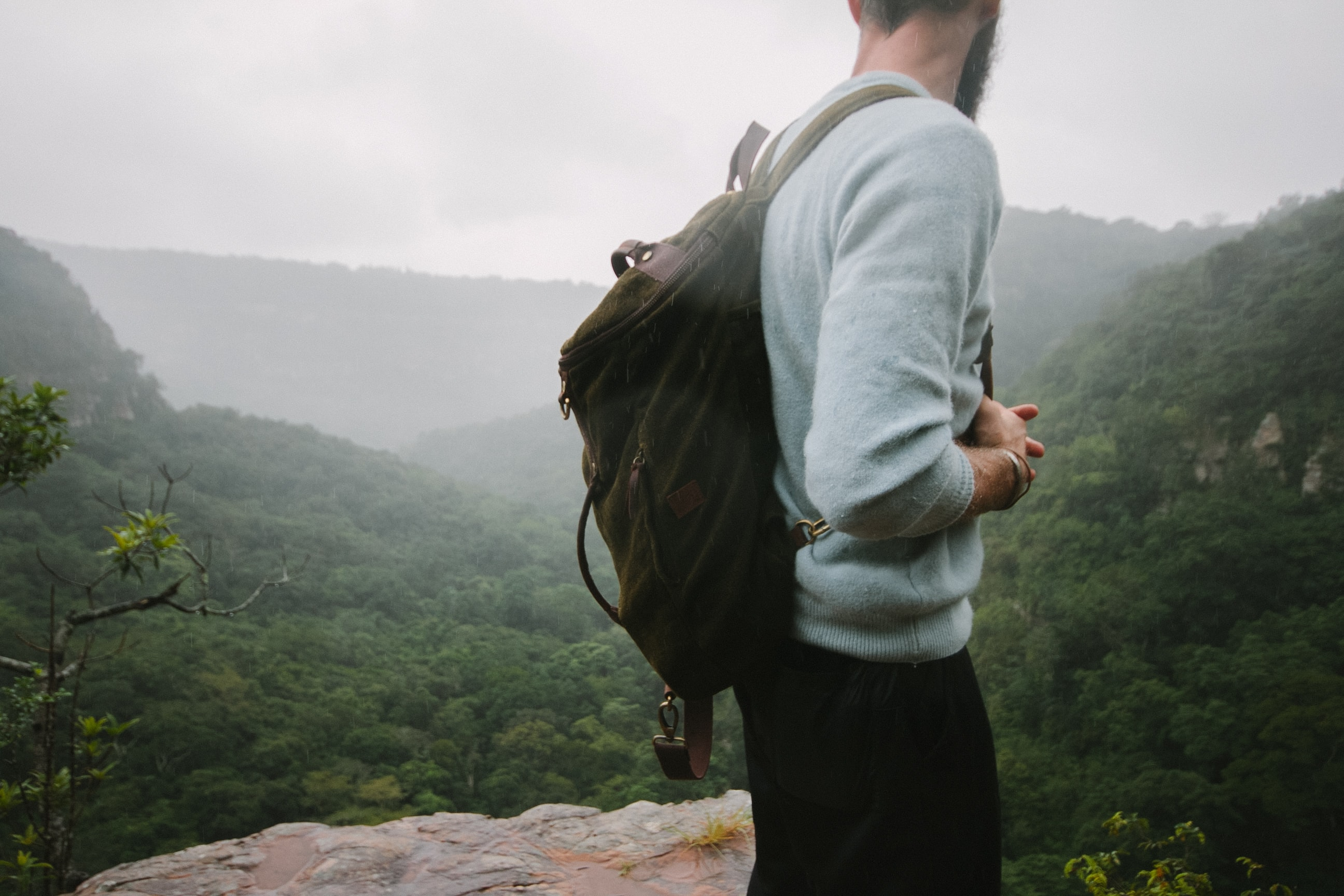man standing on mountain top during day