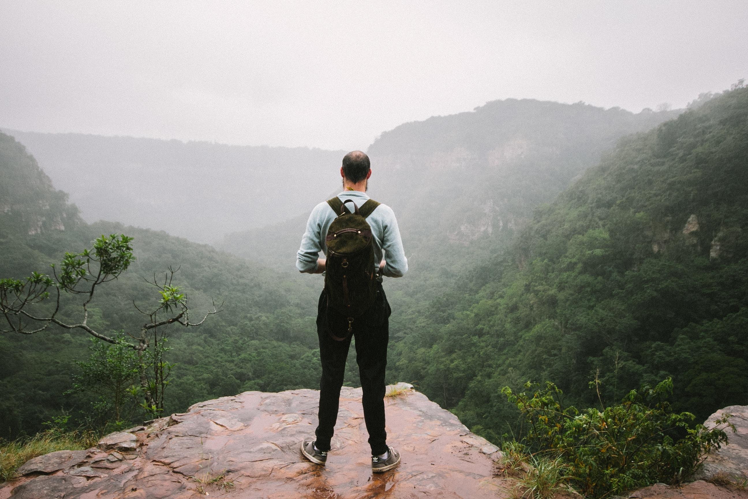 man standing near cliff overlook mountains
