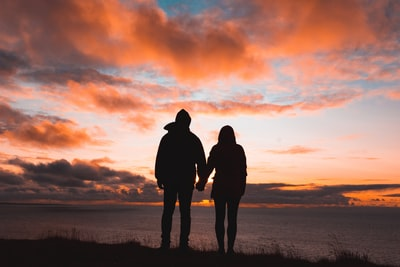 silhouette photo of man and woman on cliff couple zoom background