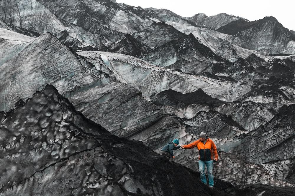person wearing orange jacket standing on rock formation