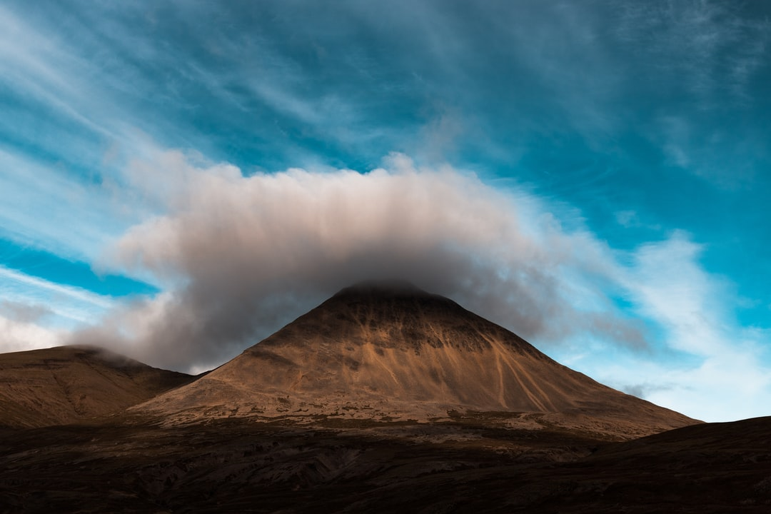 The afternoon sun set on the well known Cone Shaped Mountain in Iceland as the cloud lifted to the peak.