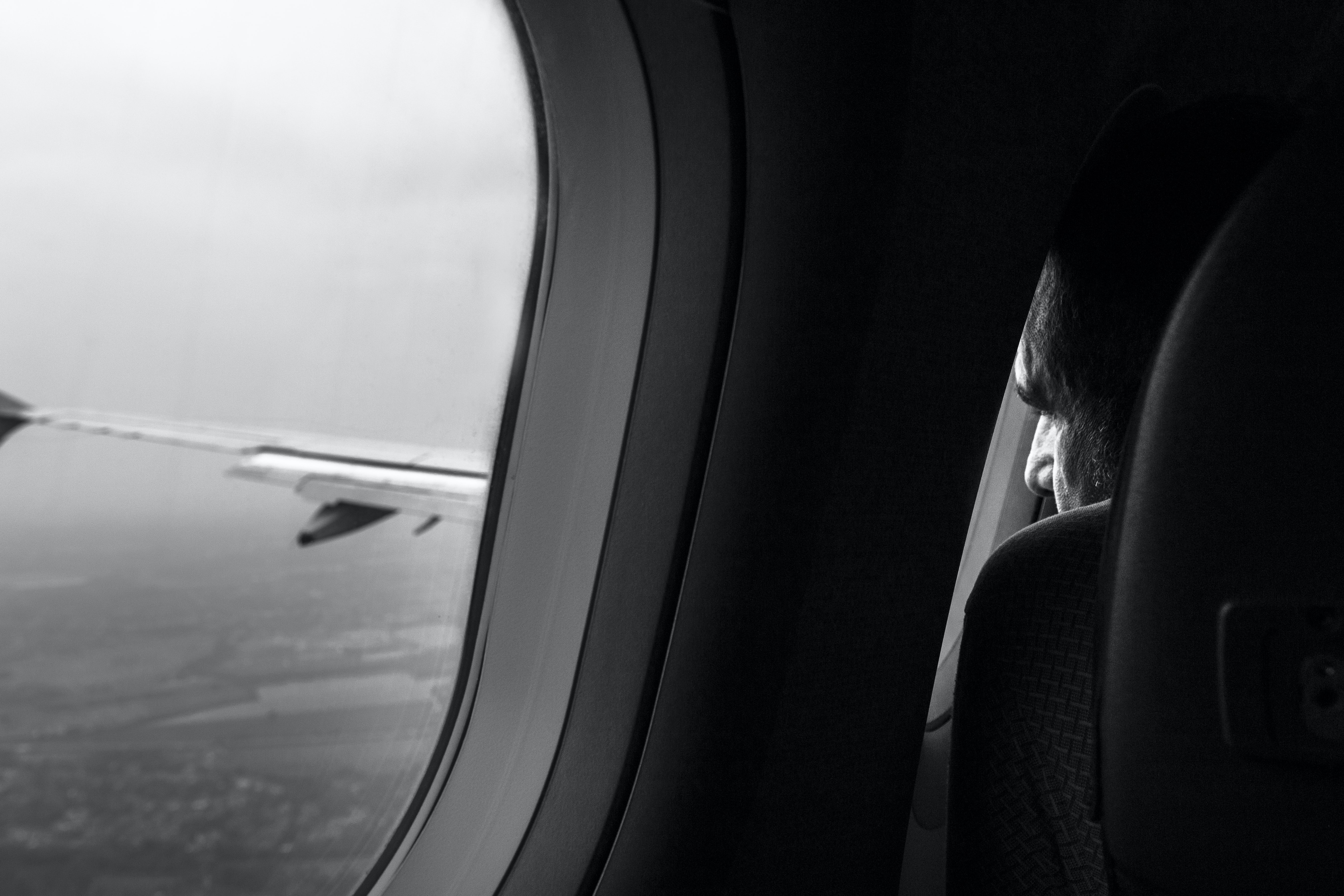 grayscale photo of man sitting near airliner window