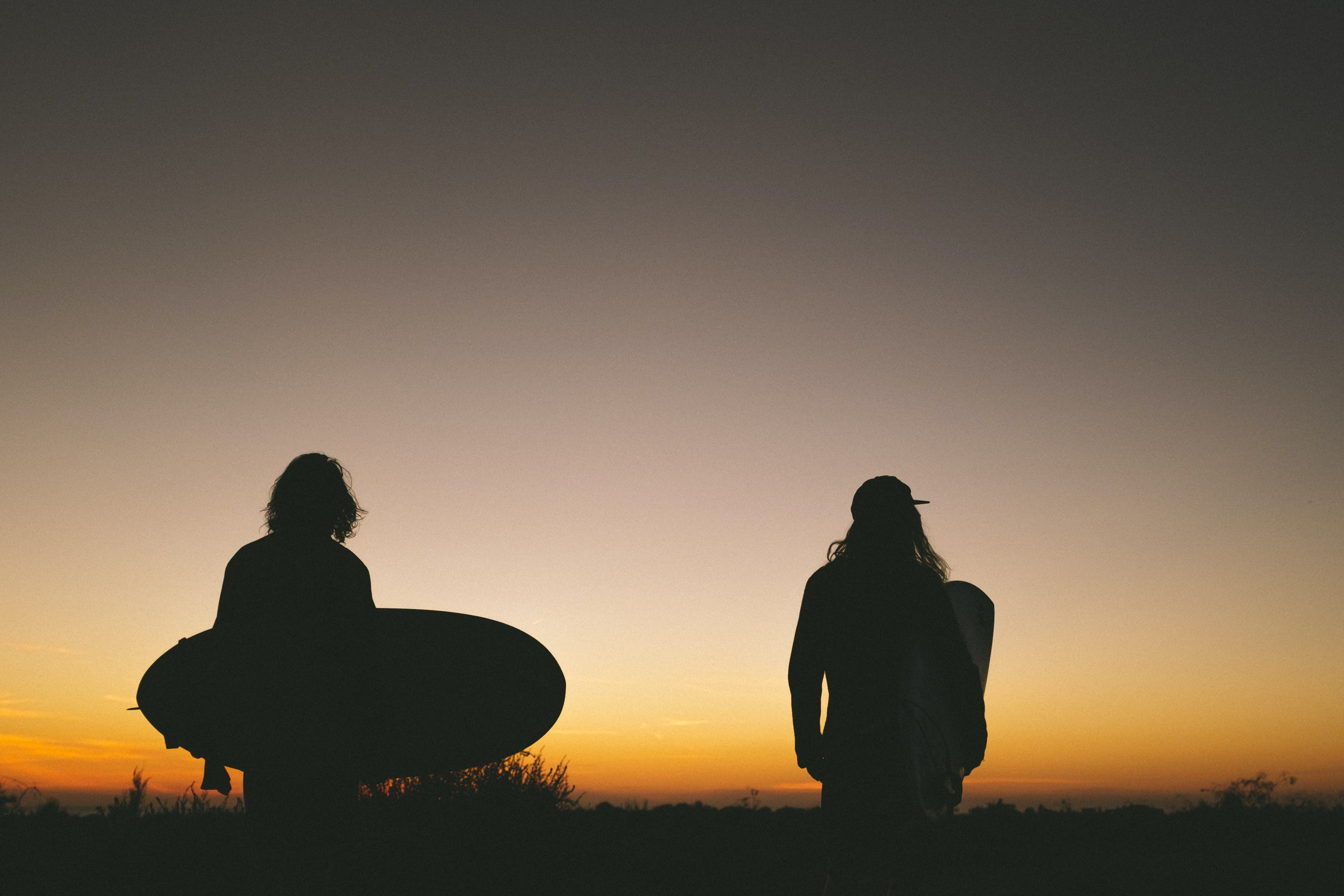 two person walking on road while holding surfboard during golden hour