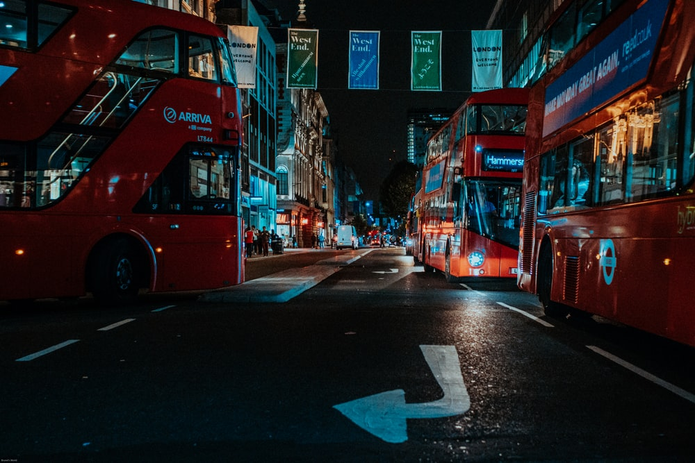 double decker buses on road at night
