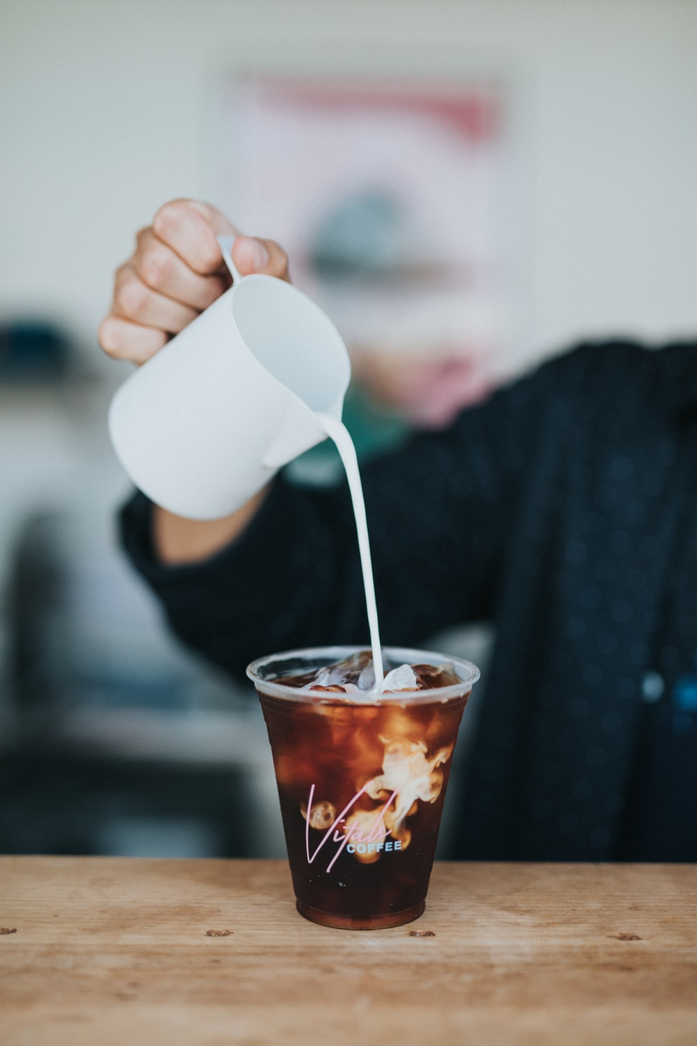selective focus photography of person holding mug pouring cream in plastic cup