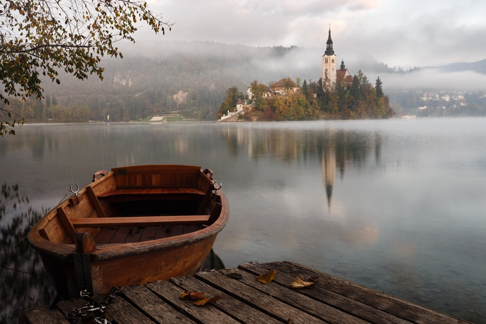 brown wooden boat floating on body of water