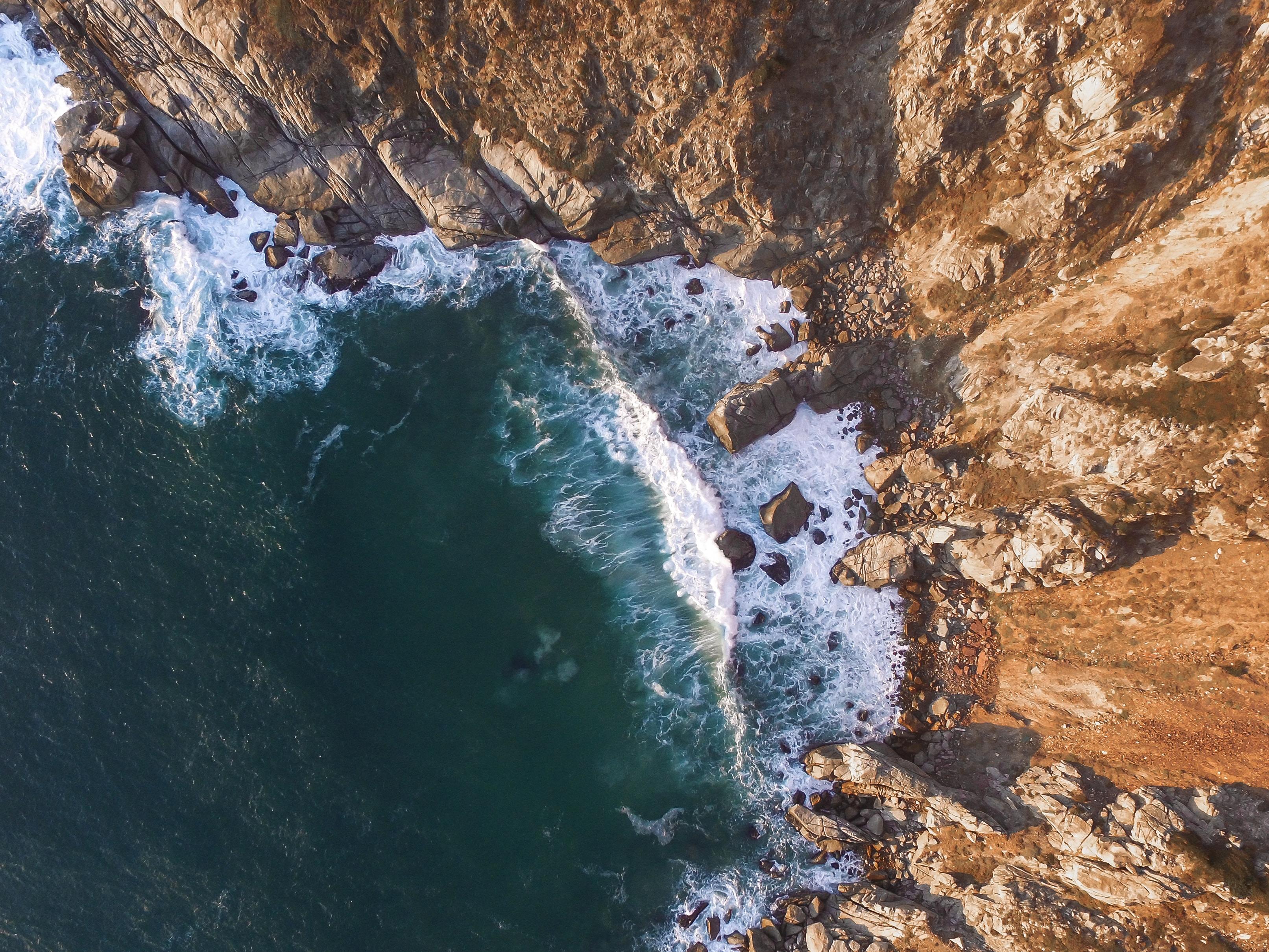 high angle photo of beach waves near mountain slope