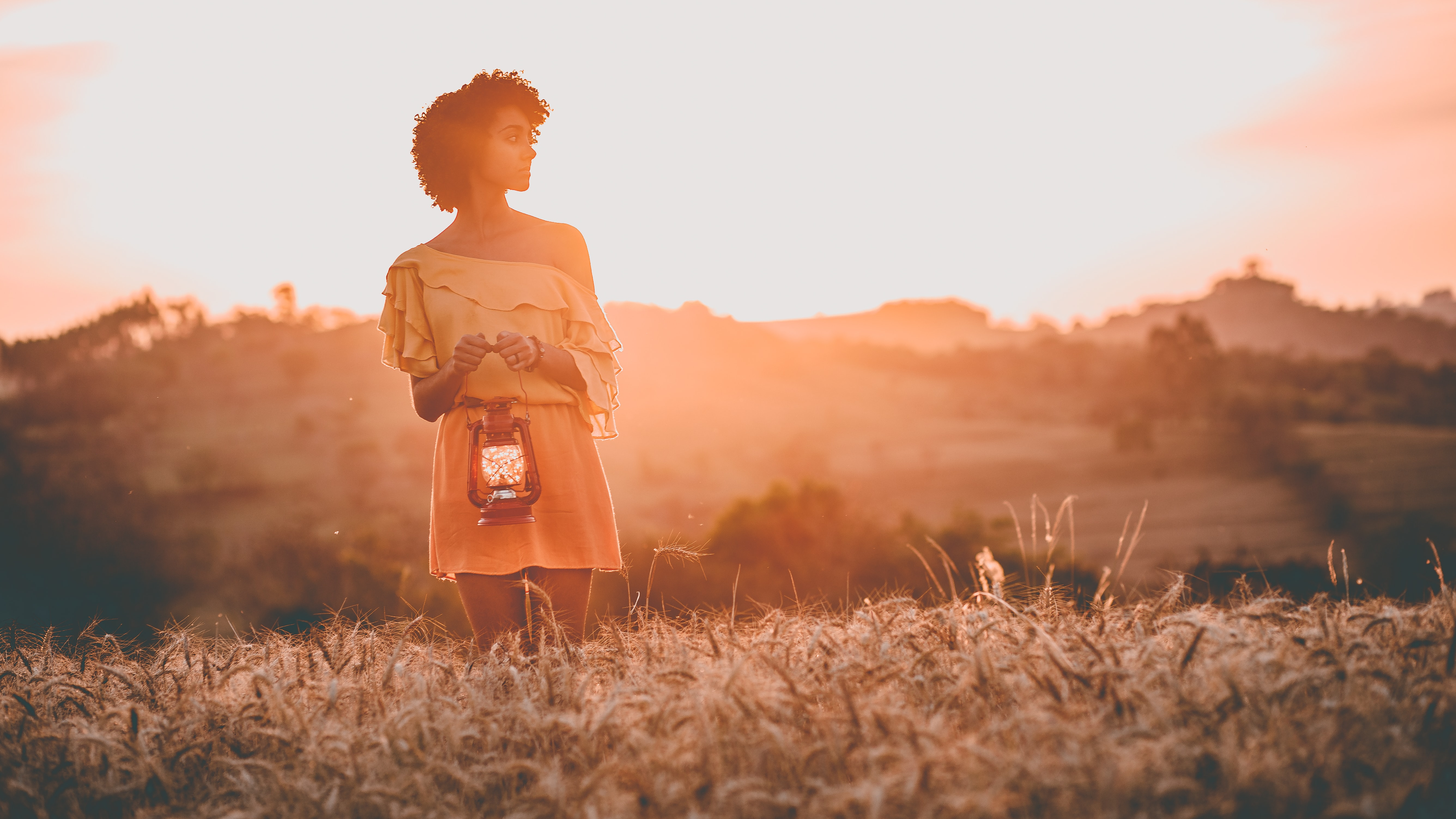 woman standing on grass field at sunset