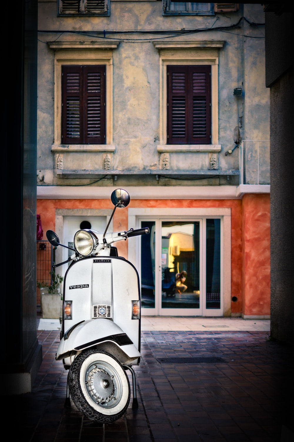 white motor scooter parked near building